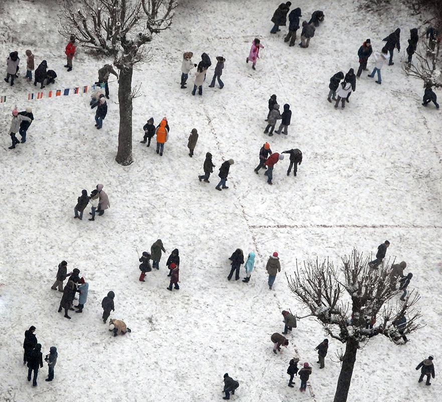 Photo tilt-shift. Dans la cour enneigée d'une école primaire, des écoliers lancent des boules de neige.