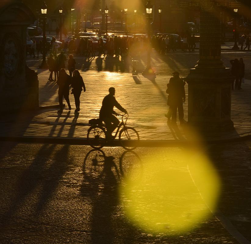 Réverbères allumés par le soleil, cycliste et ombres portées, boule de lumière tombée du ciel