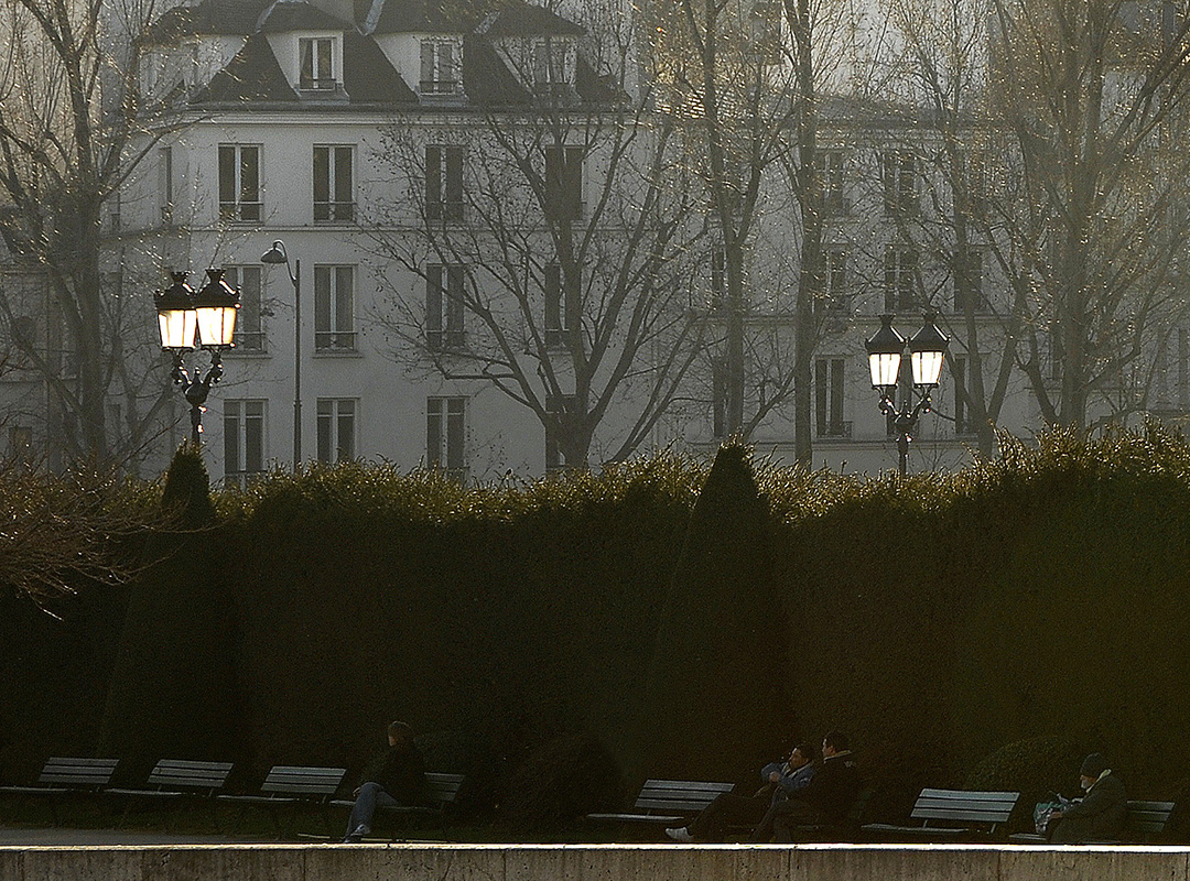 A few Parisians sitting on benches in front of two lamplighters lit up by the sun.