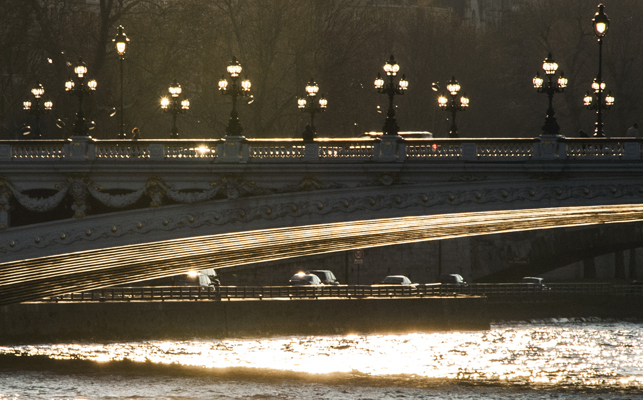 Chiaroscuro effects produced by the Sun litting up the lamplights of the bridge.