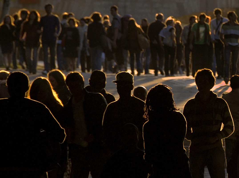 La foule de jeunes, en ombres chinoises, se rassemble au crépuscule et avance par vagues successives.