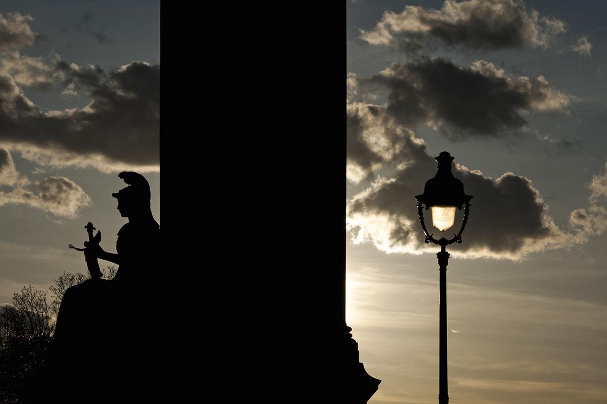 Le réverbère allumé par le soleil se dresse comme une sentinelle à côté de la femme, allégorie de la France