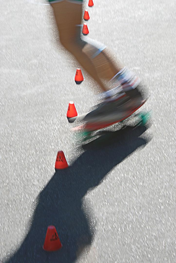 Photo de sport esthétique. Un roller passe à travers les plots de couleur vive dans un slalom acrobatique très artistique