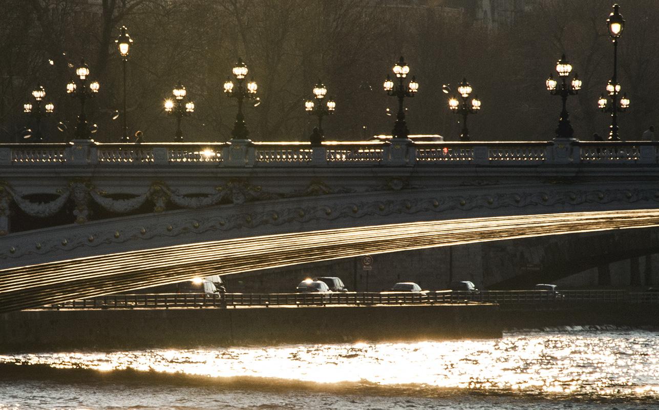 Éclairage en clair-obscur. Le soleil allume de sa lumière blanche les lampadaires du pont