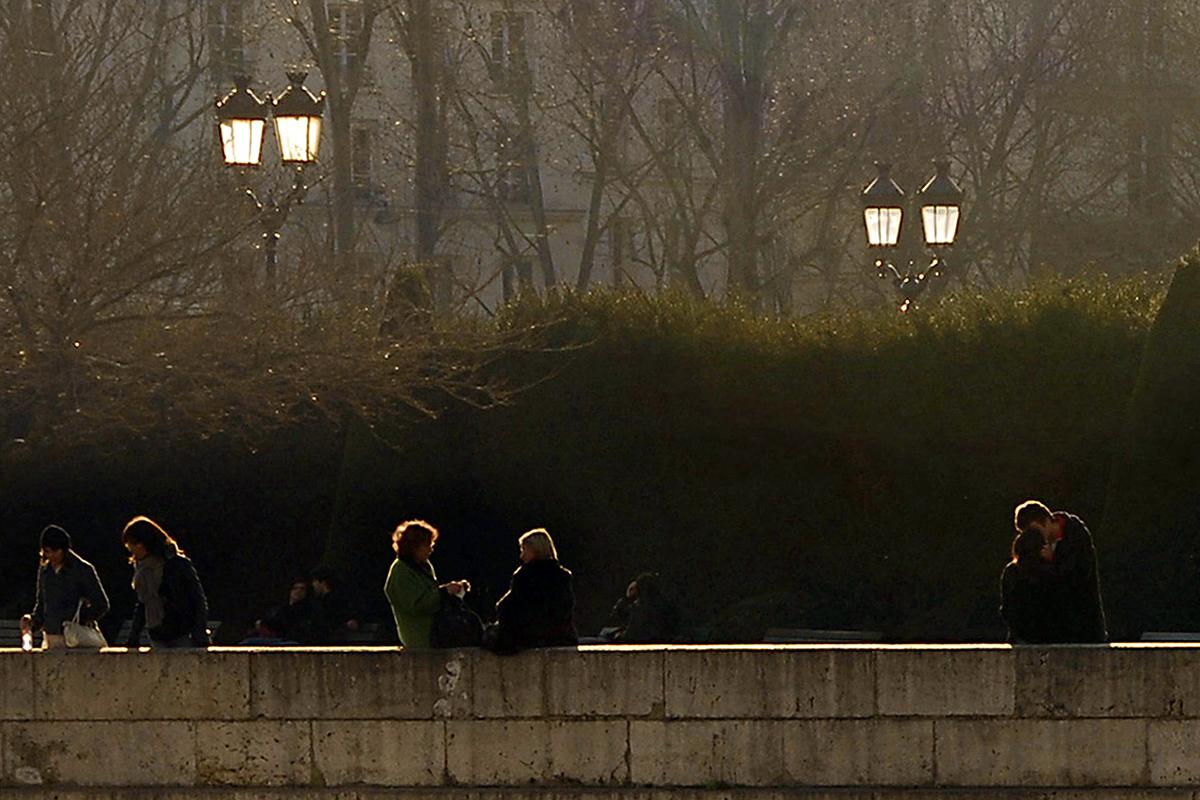 Amoureux et promeneurs goûtent la douceur de l'après-midi sous le regard des réverbères