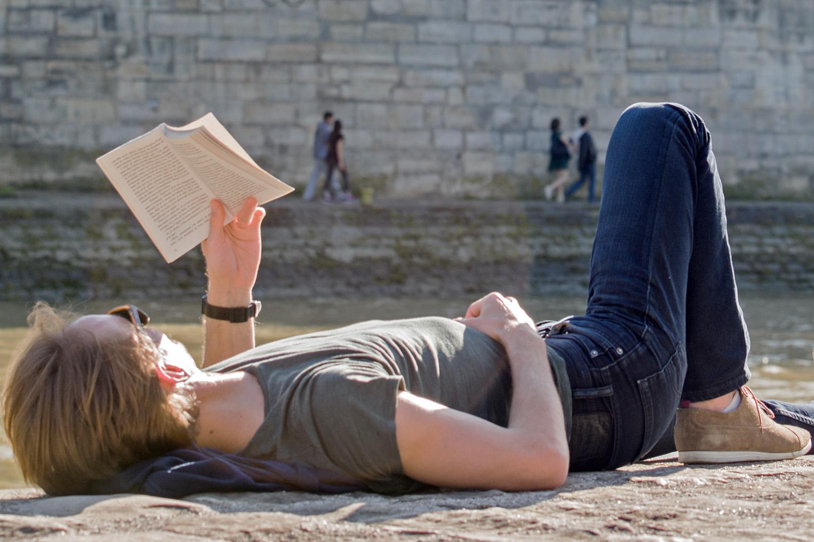 Un lecteur allongé, deux couples marchant sur la berge d'en face, personnages échappés du roman