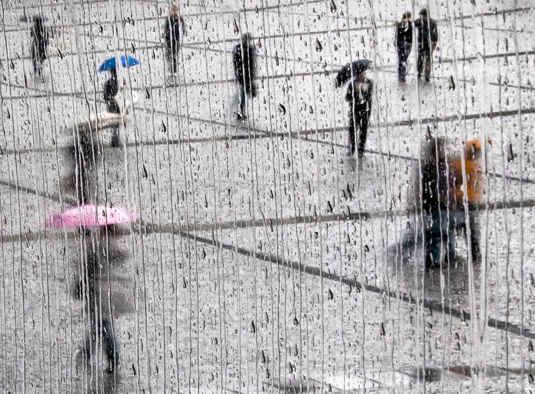 Sur le parvis quadrillé de Beaubourg, des citadins sous la pluie, avec parapluie rose ou bleu.