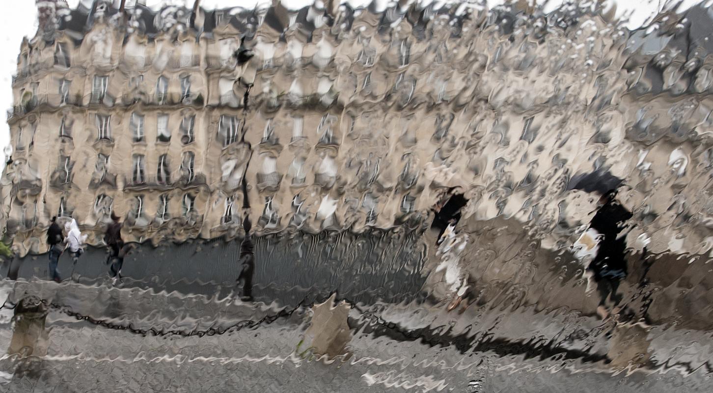 Robe Belle Époque devant les immeubles haussmanniens du quai aux Fleurs noyés sous la pluie
