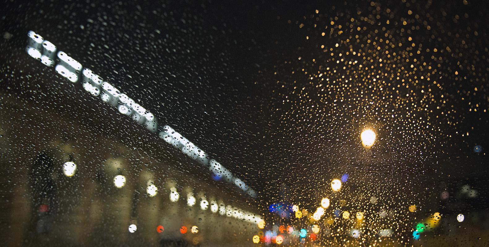 Les gouttes de pluie rayonnent comme un feu d'artifice autour des réverbères
