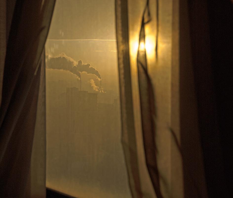Soleil visible dans les plis du rideau, lueurs matinales, ligne de l'horizon clairement dessinée.