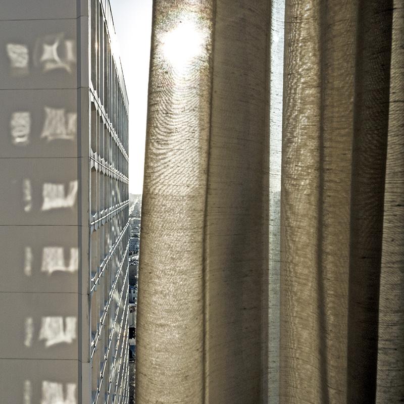 Soleil filtré par le rideau, reflets des fenêtres sur l'immeuble d'en face. Photo très graphique.