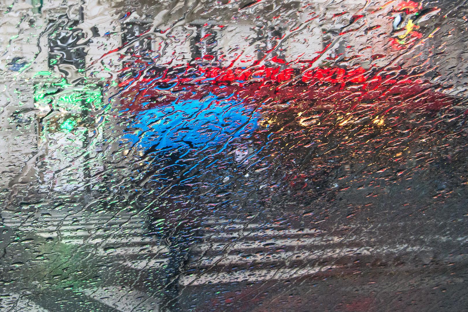 Sous une pluie abondante, le parapluie ressemble à une noix ou à un cerveau bleu. Harmonie en RVB