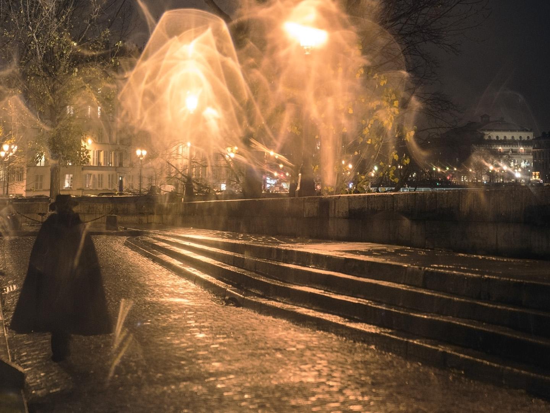 À la pointe de l'île, un homme en cape noire, dans une atmosphère fantastique, après la pluie nocturne