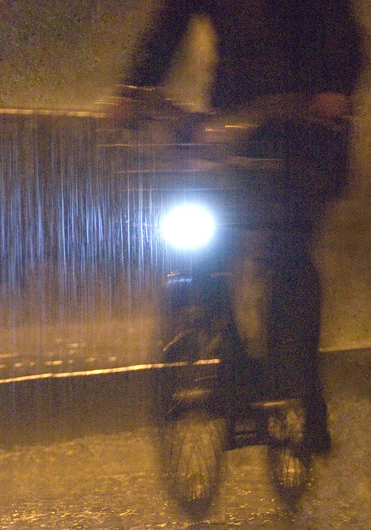 Cycliste sur Velib' sous la pluie, traînée de lumière bleue, en zigzag, effet de Light Painting