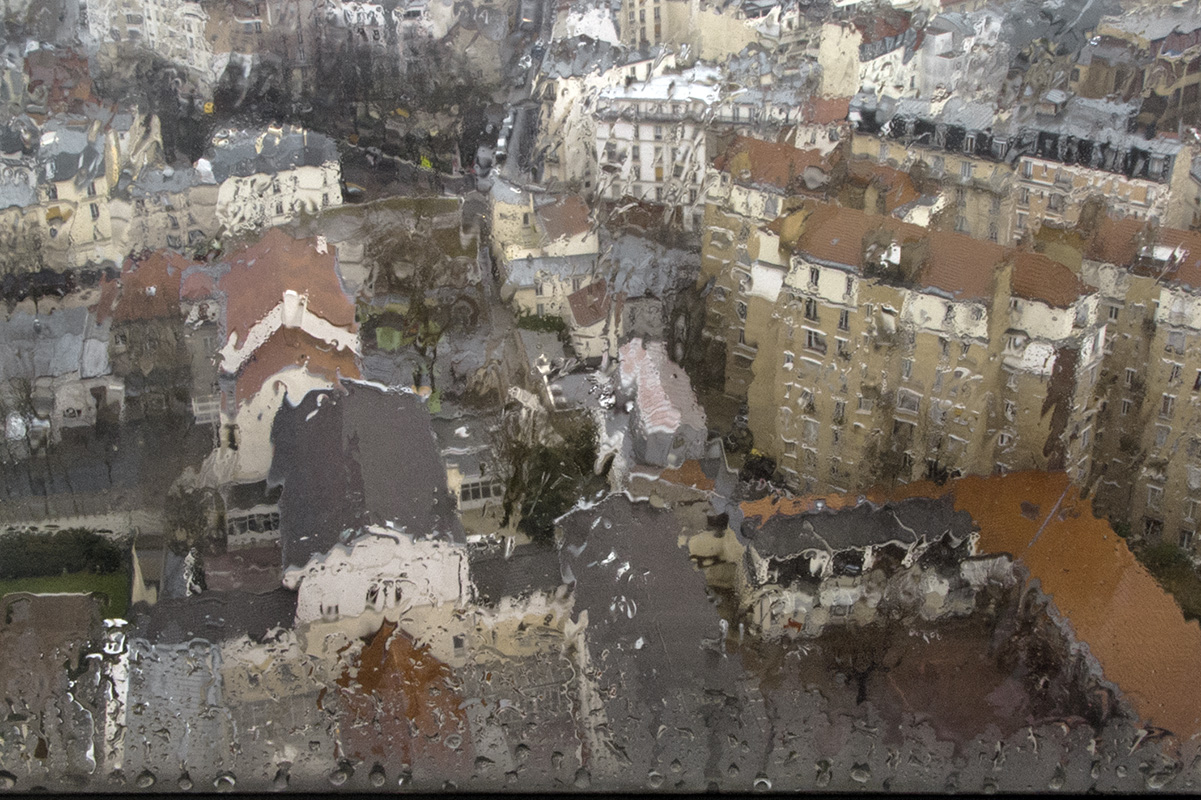 An aerial view of a schoolyard and the roofs of the Butte-aux-Cailles in the rain, through a fogged window.