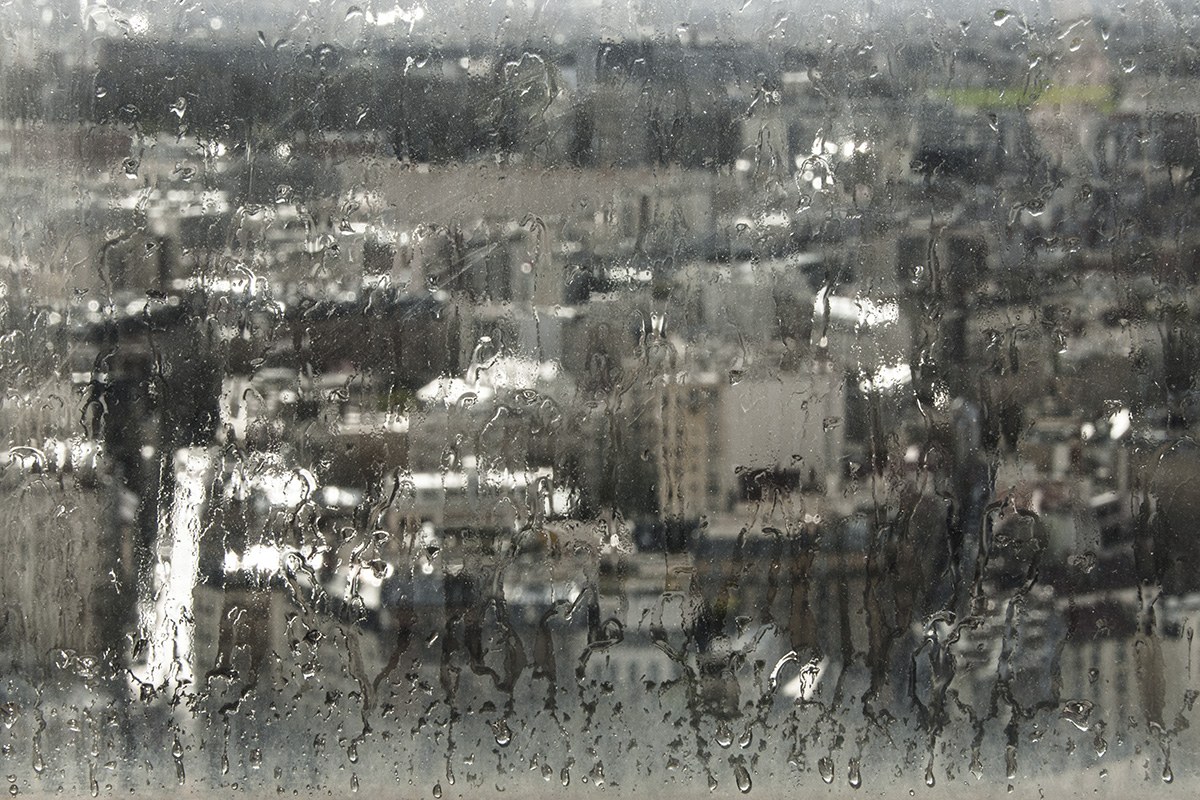 An impressionnist view of the roofs of Paris in the rain, through a fogged window.