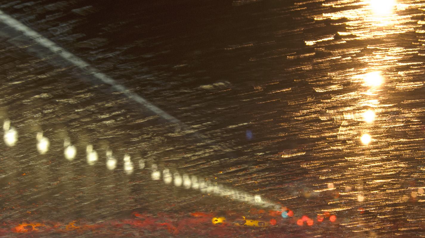 Alignement de réverbères, photo très graphique, la pluie gicle en traînées de lumière
