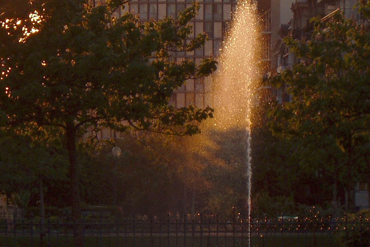 Le soleil couchant éclaire seulement la moitié du jet d'eau, qui jaillit comme une poussière lumineuse.