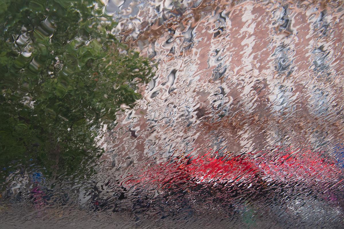 L'averse dessine un rideau de pluie et déforme les lignes d'un café parisien, place d'Italie