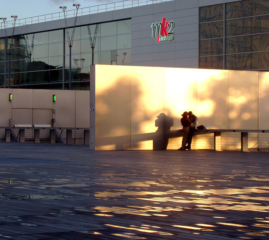 Two lovers near the BnF, the metallic wall reflects the rays of the sunset on the rain puddles.